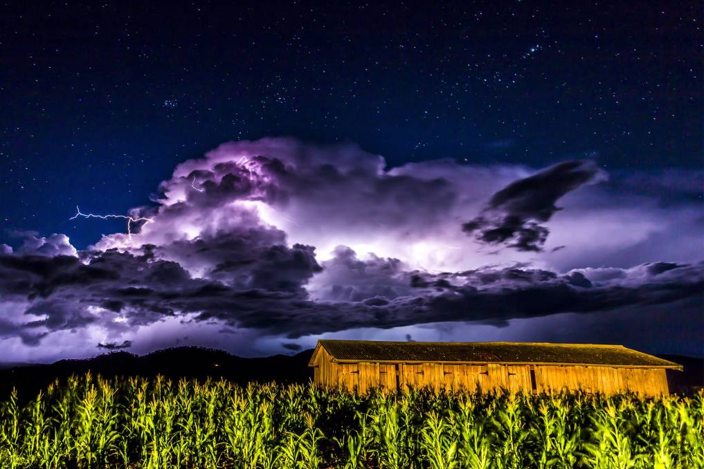 thunderstorm over grass field